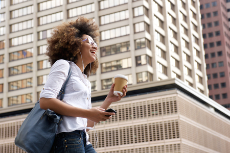 Photo pour Side portrait of a smiling african american woman walking in the city with cellphone - image libre de droit