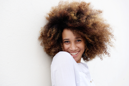 Close up portrait of a young woman smiling with afro hair against white background