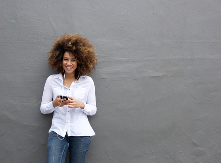 Photo pour Portrait of young african american woman with afro listening to music on smart phone - image libre de droit