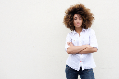 Photo pour Portrait of a cool young african american woman with curly hair standing against white background - image libre de droit