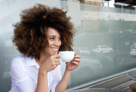 Portrait of smiling african american woman sitting with cup of coffeeの写真素材