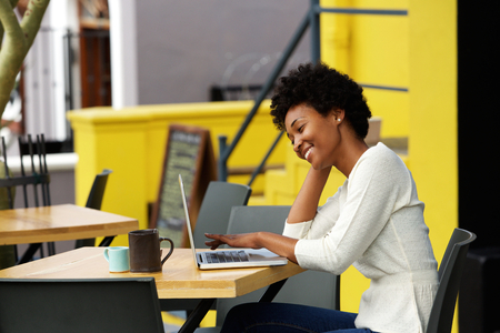 Photo for Portrait of a happy young african woman relaxing in outdoor cafe and using a laptop - Royalty Free Image
