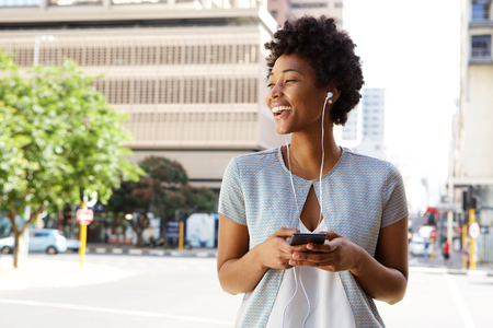 Photo pour Portrait of cheerful young lady out on the city street listening to music on her mobile phone - image libre de droit