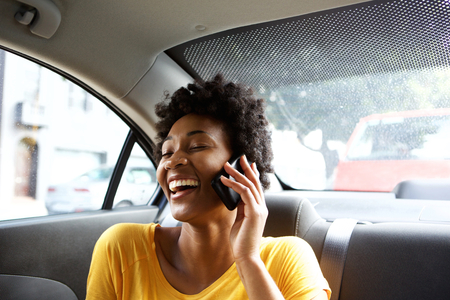 Photo pour Closeup portrait of laughing young african woman sitting on a back seat of a car and talking on mobile phone - image libre de droit