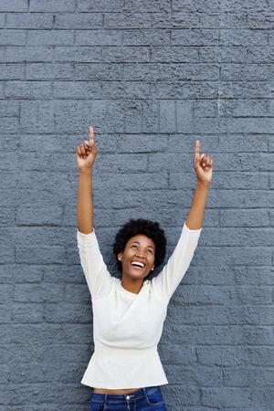 Photo pour Portrait of a smiling african woman celebrating her success against a gray wall - image libre de droit