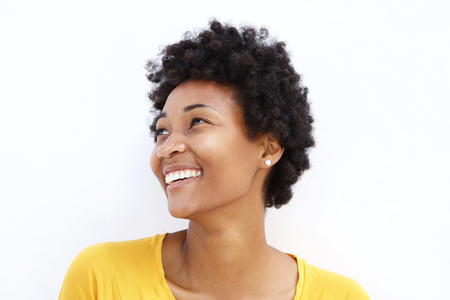 Photo for Closeup portrait of happy young african woman looking away against white background - Royalty Free Image