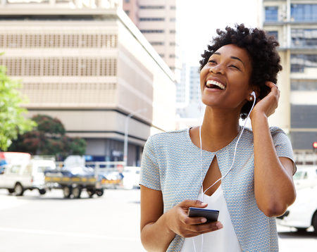 Photo pour Portrait of smiling young african american woman listening to music on headphones outdoors on city street - image libre de droit