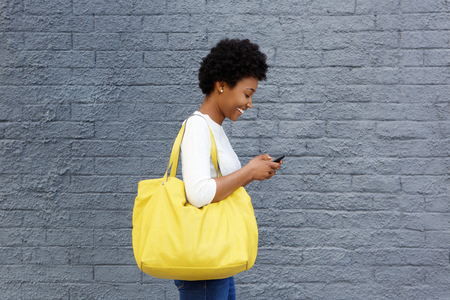 Photo for Side portrait of a happy young woman with a bag reading text message on her mobile phone - Royalty Free Image