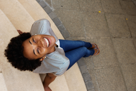 Photo for Overhead portrait of smiling young african woman sitting on steps and looking up - Royalty Free Image
