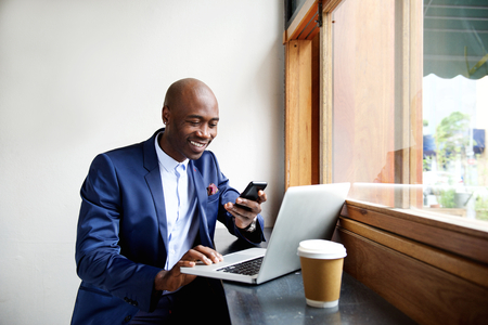 Photo for Portrait of happy african businessman using phone while working on laptop in a restaurant - Royalty Free Image