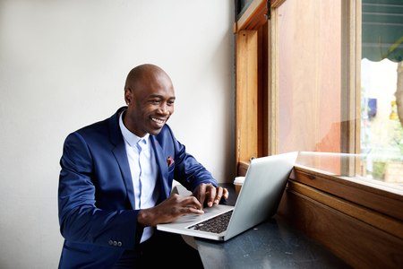 Photo pour Portrait of happy african businessman sitting in a cafe and working on laptop - image libre de droit
