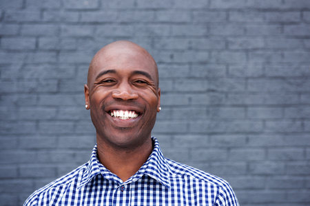 Photo pour Close up portrait of smiling african man standing against a gray wall - image libre de droit