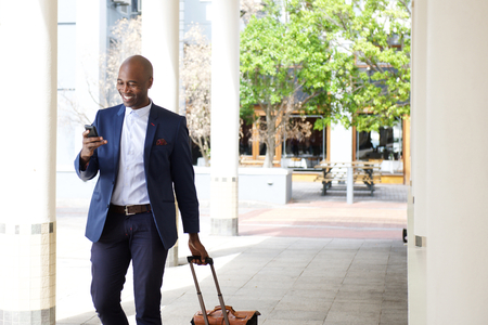 Foto per Portrait of businessman traveling with a bag and mobile phone - Immagine Royalty Free