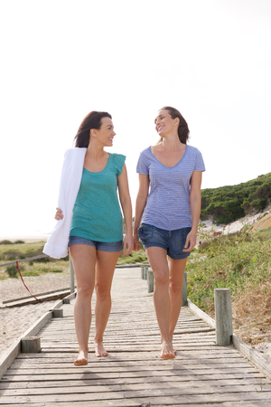 Full length portrait of two female friends walking from the beachの写真素材