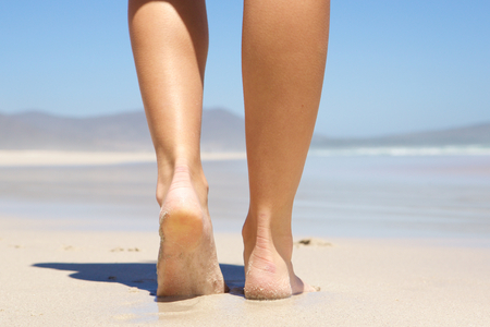 Low angle woman walking barefoot on beach from behind