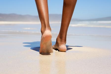 Photo pour Low angle woman walking barefoot on beach - image libre de droit