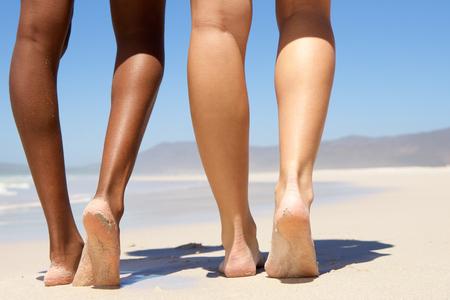 Low angle two women walking barefoot on beach