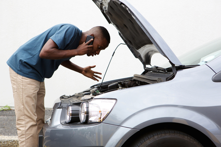 Photo pour Side portrait of a young african man having trouble with his broken car calling for help on cell phone. - image libre de droit