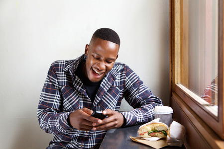 Photo for Portrait of smiling young african man sitting at a cafe and reading text message on his cell phone - Royalty Free Image