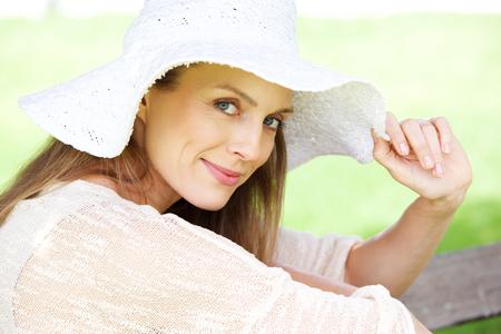 Photo pour Close up portrait of a beautiful older woman smiling with hat - image libre de droit
