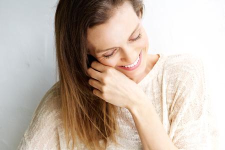 Foto für Close up candid portrait of a woman laughing against white background - Lizenzfreies Bild