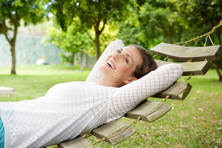Foto de Portrait of a smiling older woman relaxing on hammock outdoors - Imagen libre de derechos
