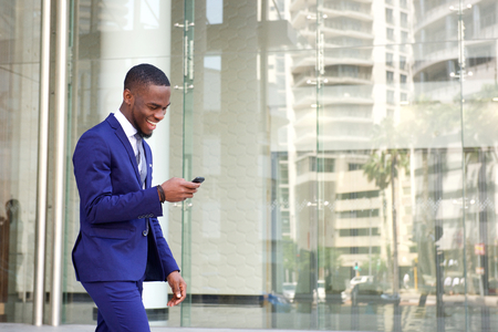 Photo for Side portrait of a happy young man in suit walking and reading text message on his mobile phone - Royalty Free Image