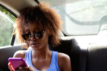 Close up portrait of a young african american woman sitting n backseat of car looking at cell phone