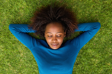 Photo for Portrait from above of a young african woman lying on grass sleeping - Royalty Free Image
