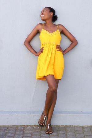 Photo pour Full length portrait of a african female fashion model smiling in yellow dress - image libre de droit
