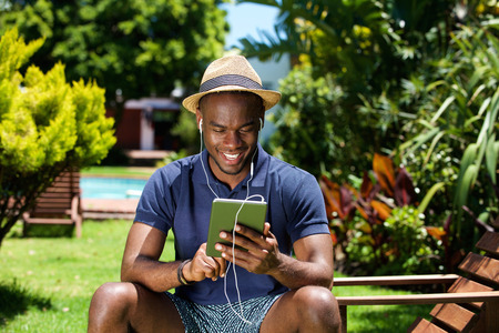Photo pour Portrait of a smiling young african man sitting outdoors using digital tablet - image libre de droit