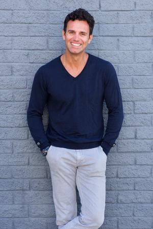 Photo pour Portrait of a confident man smiling against gray wall - image libre de droit