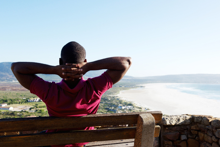 Rear view portrait of young african man sitting relaxed on a bench with his hands behind head, young guy on vacation.の写真素材