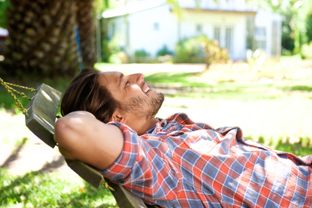 Photo pour Portrait of an attractive man lying down in hammock in back yard - image libre de droit