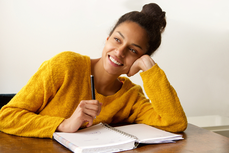 Portrait of a smiling female student thinking with with pen and paper