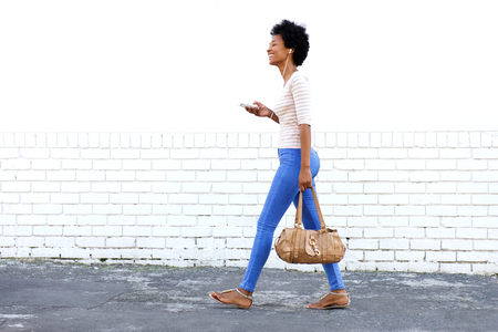 Foto de Full length portrait of beautiful woman walking outdoors listening to music with purse - Imagen libre de derechos
