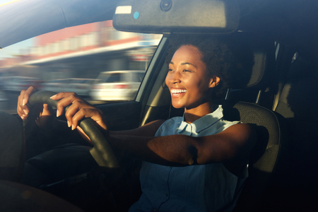 Portrait of smiling young african american woman driving a carの写真素材