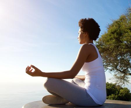 Photo pour Side portrait of beautiful young woman sitting in yoga pose at beach - image libre de droit