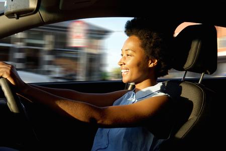 Foto de Side portrait of happy young african woman driver driving a car - Imagen libre de derechos