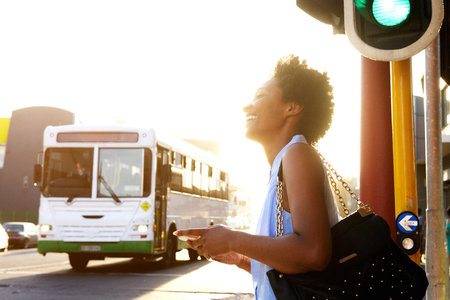 Photo pour Close up side portrait of smiling african american woman with cell phone on the city street - image libre de droit