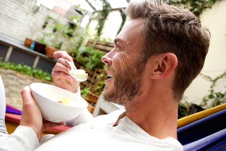 Photo pour Close up side profile portrait of happy man eating fruit salad outside - image libre de droit