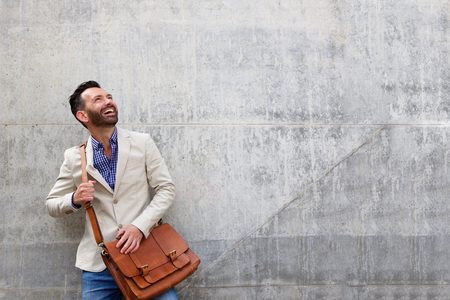 Photo pour Portrait of handsome middle aged guy standing against wall looking away at copy space and smiling - image libre de droit