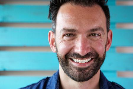 Foto de Close up portrait of handsome mature man with beard smiling - Imagen libre de derechos
