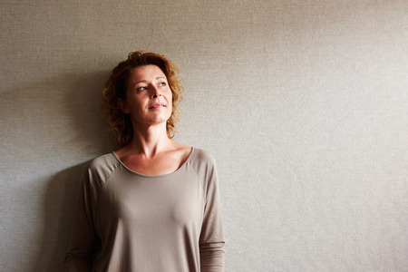 Portrait of woman with curly hair leaning on wall in contemplation