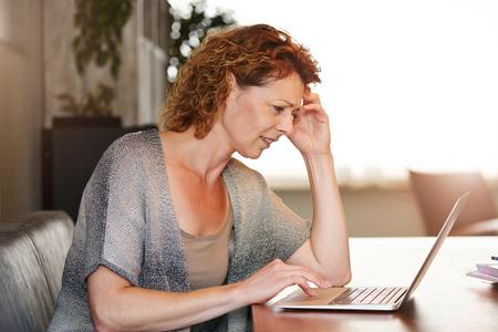 Foto für Portrait of woman looking at computer thinking sitting at table - Lizenzfreies Bild