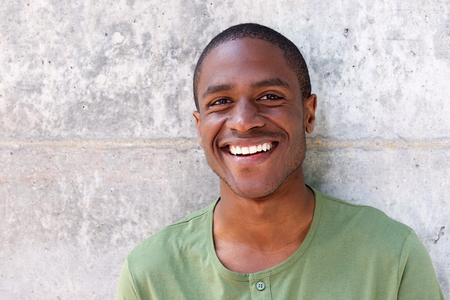 Close up portrait of cheerful young black man smiling against wall