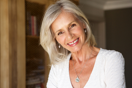 Foto per Close up portrait of beautiful older woman standing in study smiling - Immagine Royalty Free