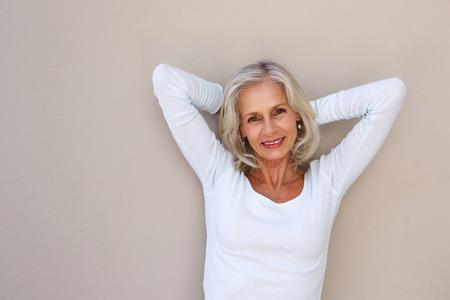 Foto für Portrait of smiling carefree older woman with hands by head - Lizenzfreies Bild