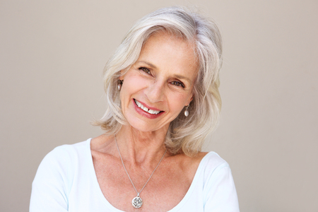 Foto per Close up portrait of beautiful older woman smiling and standing by wall - Immagine Royalty Free
