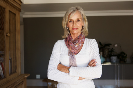 Photo pour Portrait of serious older woman standing in study with arms crossed - image libre de droit